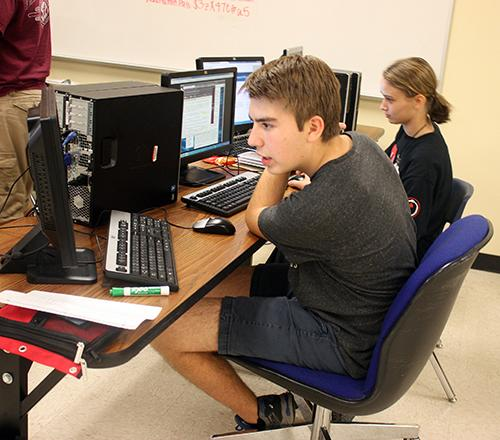Sophomore Lucas Stewart and senior Hayley Morgan create firewalls to stop cyber attacks. The Cyberpatriot program prepares students for technology related careers. Photo by: Kaylin Kline