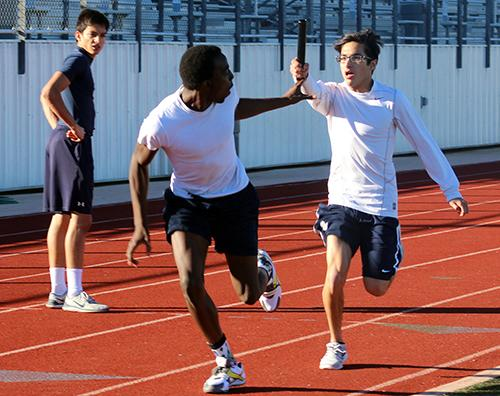 Sophomore De'Jaughn Padonu (left) and junior Phillip Sanchez-Torres pass the baton during a practice relay on Feb. 24.