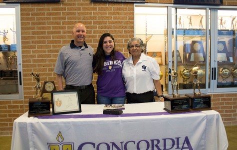 Flanked by her golf coaches Jason Pape and Delia Alderete, senior Holly Mendez signs her letter of intent to play golf at Concordia University March 8 in the  main gym foyer.