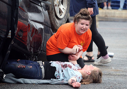 Portraying victims of a drunk driving crash, senior Emily Harrison cries over victim Hannah Pittman during Shattered Dreams. Accidents also can occur form distracted driving.