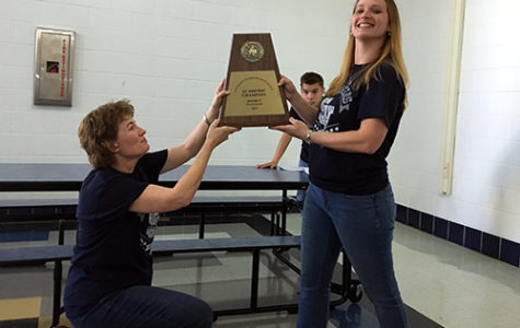 Former UIL coordinator Denise Nipper and current UIL coordinator L. Sellers hold up the first place academic team plaque while sophomore Niles Nelson watches in the background.