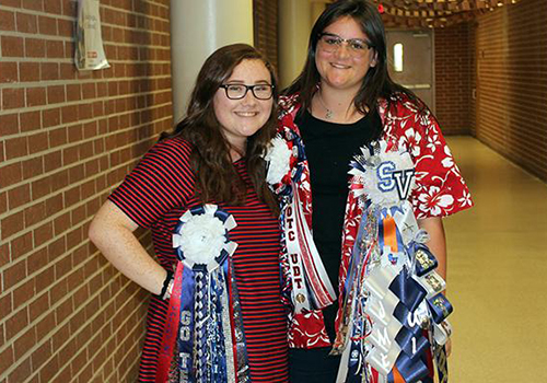 Sophomores Lyndsey Reyes and Jaymie Nickles smile with mums galore in C wing.