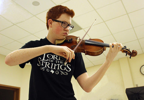Anthony Couvillion plays his violin before school in the choir room.