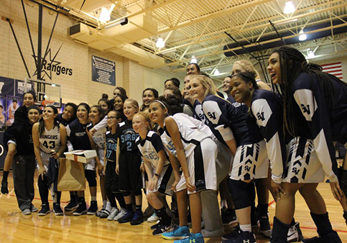 The varsity girls basketball team poses with junior athletes during half time. They defeated East Central 50 - 32.