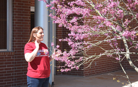 Librarian Amanda Trussell enjoys the first day of spring outside with the Texas Redbuds outside of the library on March 20.