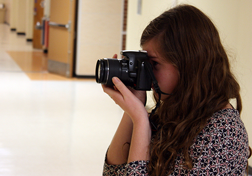 Senior Emma Sipple takes pictures for a prom story in A-wing on April 2.
