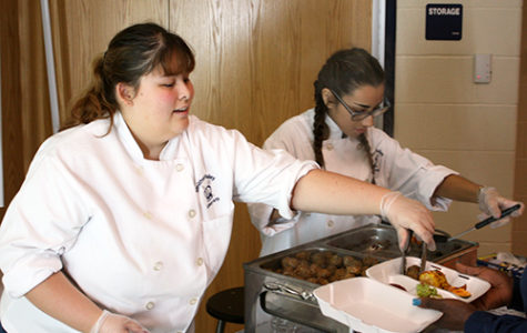 Senior Chantelle Cresswell and Isaelle Ramirez serve Barbacue beef meatballs and mini chicken and cheese enchiladas.
