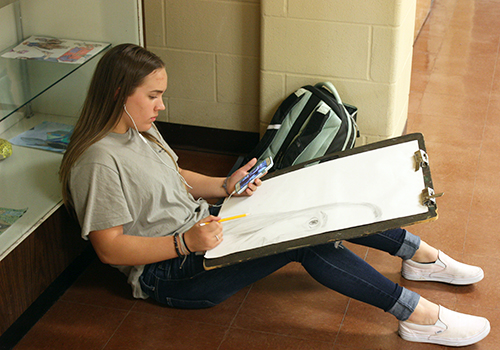 Sophomore Avery Streitz works on a self portrait for  her art class on May 11.