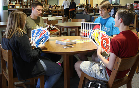 Seniors Jonathan Owen, Lucas Stewart, Logan Garner and Cassandra Frazier play a game a giant uno in the library durring their off period on May 11.