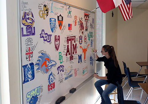 On her last day on campus, senior Sidney Clark draws her college emblem on the designated senior board in teacher Kathryn Rutledge's classroom in D wing on May 29.