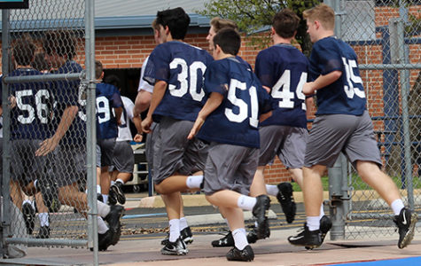 The freshmen football team runs back to the field house after the end of their practice to get ready to go home.