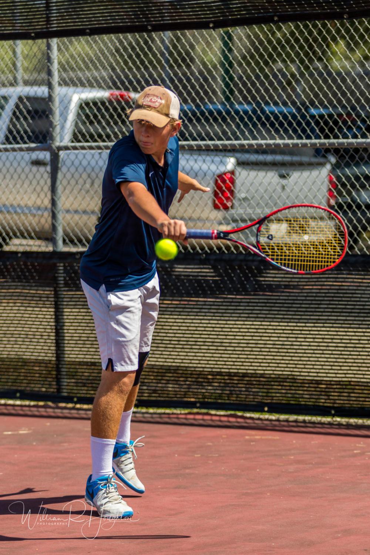 Junior tennis player, Grady Payne strikes ball at Bi District tournament on April 27.