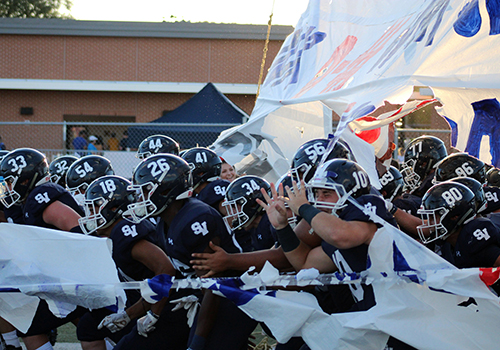The football team roars onto the field before the season opener against Midland Lee on Aug. 31