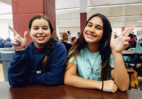 Freshmen Anna Vig and Aleena Fusse hold up two different Ranger symbols in the cafeteria on Sept. 21.