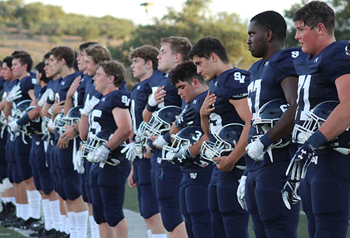 The football team stands for the national anthem before the first home game on Aug. 30.