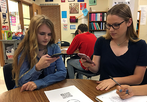 Senior Kaylin Kline and junior Jacquelyne LaFond prepare for their first FACS friend visits by testing the QR code scanner on their phones.