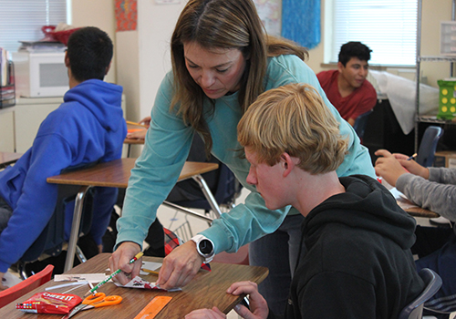 With Cheez-Its, scissor and pencil on hand, math teacher Claudia Soliz demonstrates how to use angles to create boxes.