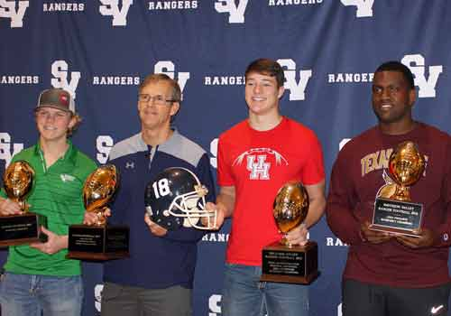PHOTO OF THE DAY: With trophies in hand, seniors Mason Reid, Levi Williams and Ronald Copney celebrate their signing day with coach Larry Hill. Reid signed with the University of North Texas, Williams with the University of Houston and Copney with Texas State University.