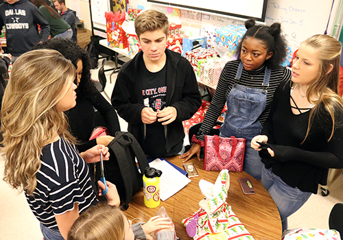 After they finished wrapping a toddler toy, seniors Kaylin Kline, Mckelvie Maxwell, Rebecca Covington, Grayson Cofield and junior Ayden Correa talk about their upcoming finals.