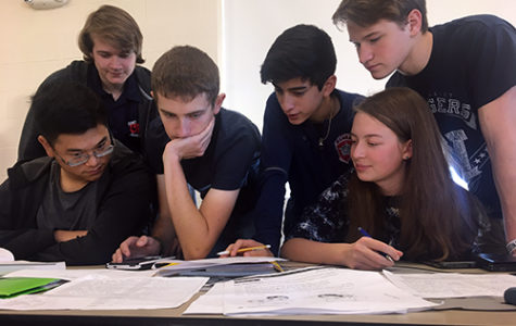 Senior Luke Estes assists math and science competitors as they wait for their next event in the Bandera High School cafeteria on Dec. 1. Senior Ross Stoutamyer and junior Audrey Pauletti are both on the right.