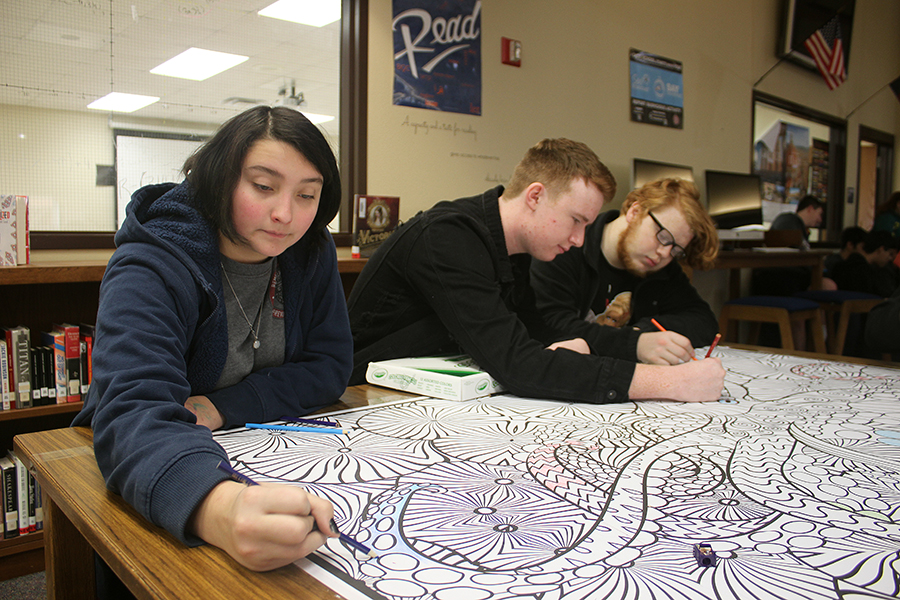 Before school, junior Josephine Ford, Max Oliver and Liahm Nowak add their artistic touches to the giant coloring page in the library. A box of colored pencils invites all who pass to participate.