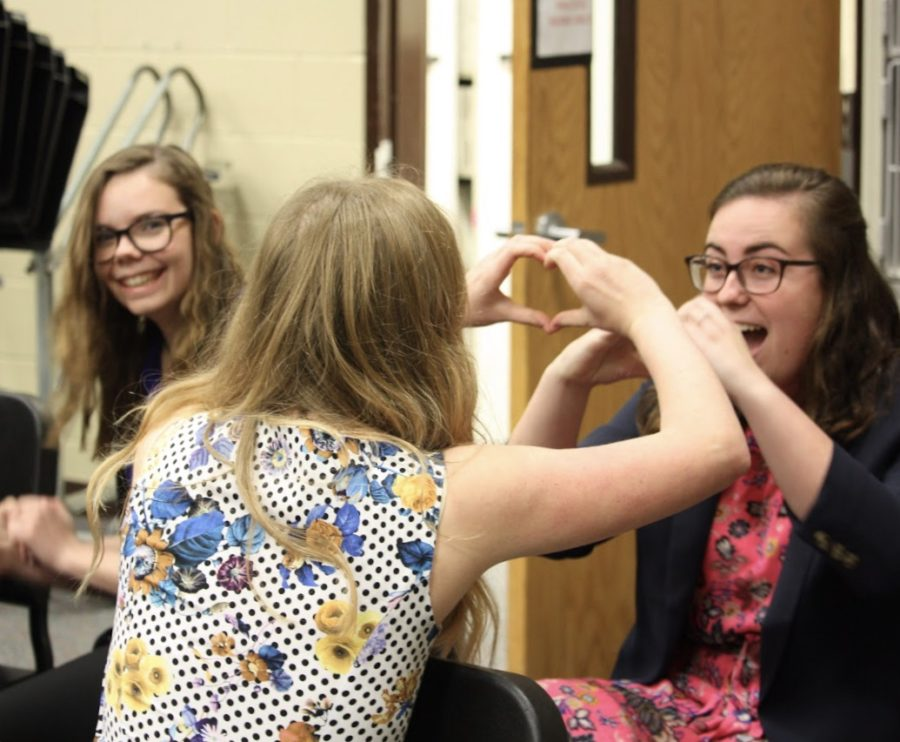 Juniors Caroline Kuhn and Rileigh Mccullough decompress prior to auditions while sophomore Maya McBrayer smiles on.