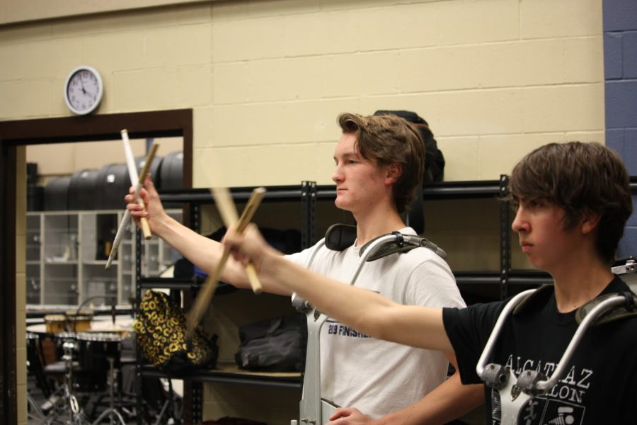 Junior percussionists William Yancosek and Mark Olaez swing their arms in time with the alma mater.