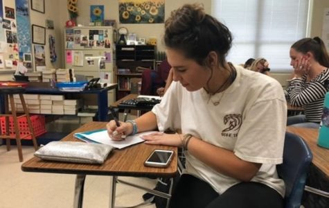 Senior Kayleigh Petray in her fifth period English class, writing in her preferred handwriting style.