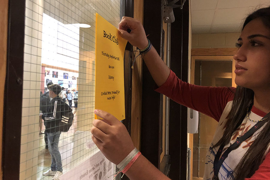 Marissa Meisner, library aide, hangs Book Club sign in the library in preparation for the first meeting 8 a.m. Thursday.