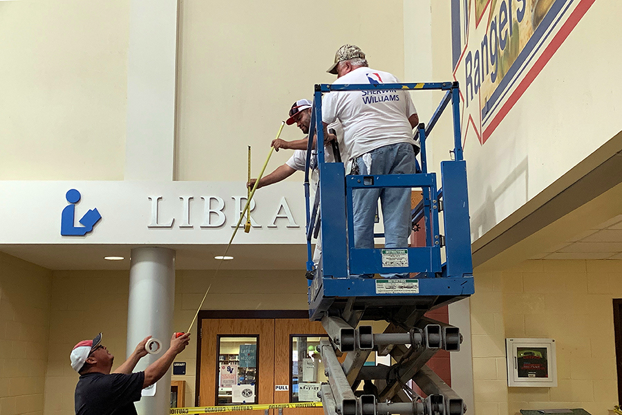 On a scissor lift in fron the Ranger mural near the library, mainentance workers Bill Logan and Rene Lopez prepare to paint over the Ranger mural in downstairs B wing Friday morning. The mural was replaced with a blue square that will bear white vinyl lettering with an SV and Rise Above in white.