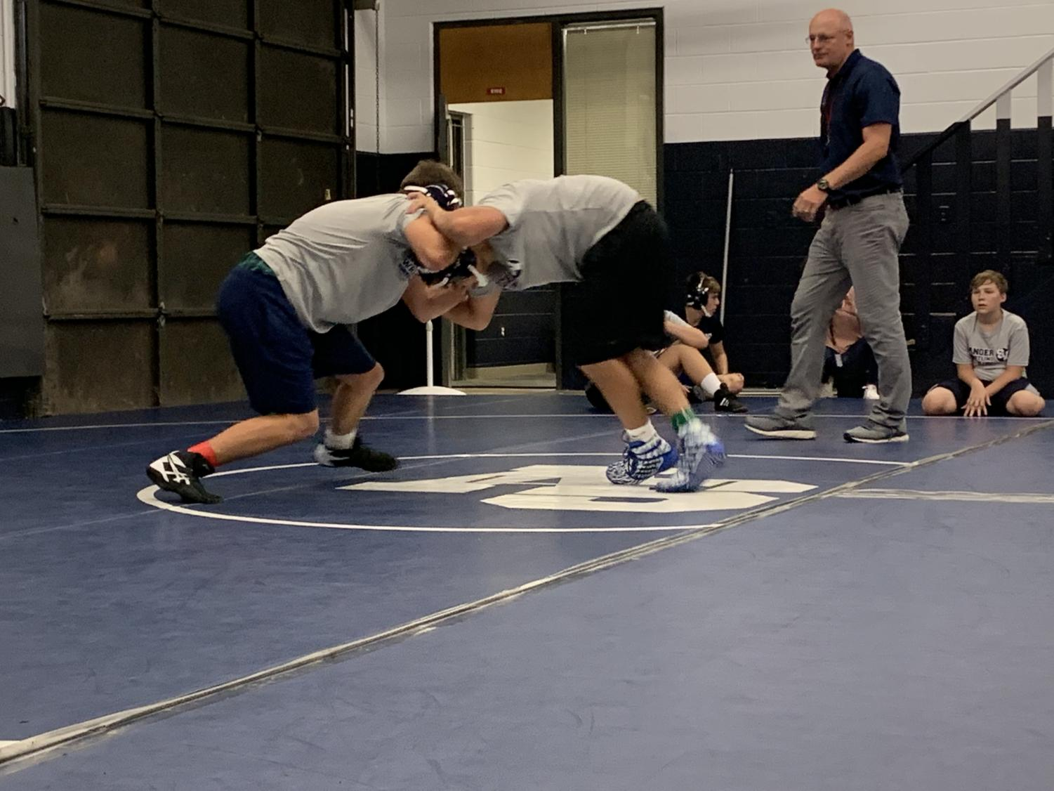 Under the watchful eye of coach Tim Clarkson, junior varsity wrestlers practice their techniques during first period on Friday.