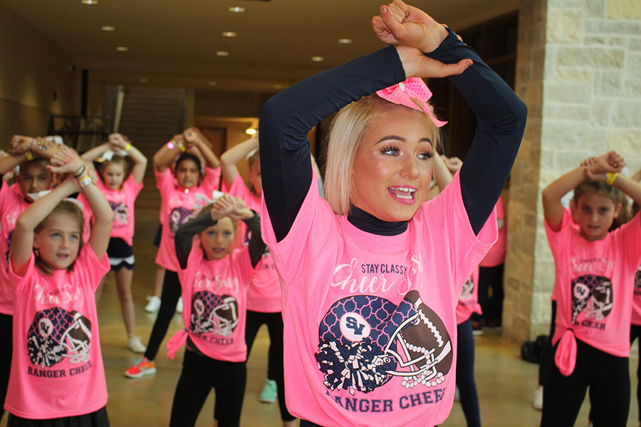 Demonstrating a cheer during the 2018 cheer clinic, senior Kamryn Moore leads a group of kindergartners through eigth graders. The 2019 clinic will take place Oct. 19 at the school.