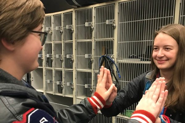 Before the start of school, seniors Carsyn Chambers (left) and Audrey Pauletti (right) share a moment of friendship in the band hall.