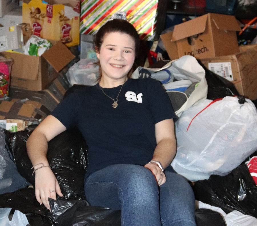 In+the+middle+of+a+day%27s+worth+of+gathering+shoes%2C+Redin+lounges+atop+a+heap+of+donated+shoes.+