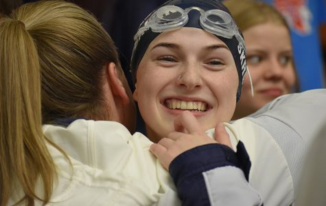 Hugging Coach Kari Osborne, sophomore Laney Skrobanek celebrates her gold medal finish in the 100 meter backstroke at the region meet Saturday at the Josh Davis Natatorium.