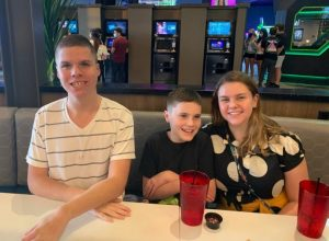 Drew, Jack, and Elle Suermann enjoy a family outing at a bowling alley.