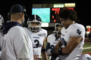 Defensive linemen Diego Hamilton (left) and Trey Moore (right) discuss tactics on the sideline. The defense will have their hands full Friday against a Westlake team averaging 54.9 points per game.
