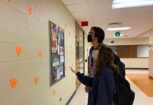 Grace Bush and Alex Dewees search for their valentine hearts in the halls. Student council put up a heart for every student and faculty member though the hallways.