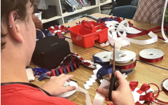 Floral design student Mayson Goodwin laughs and makes homecoming mums for the upcoming game. They made the mums to keep or donate to fellow classmates.